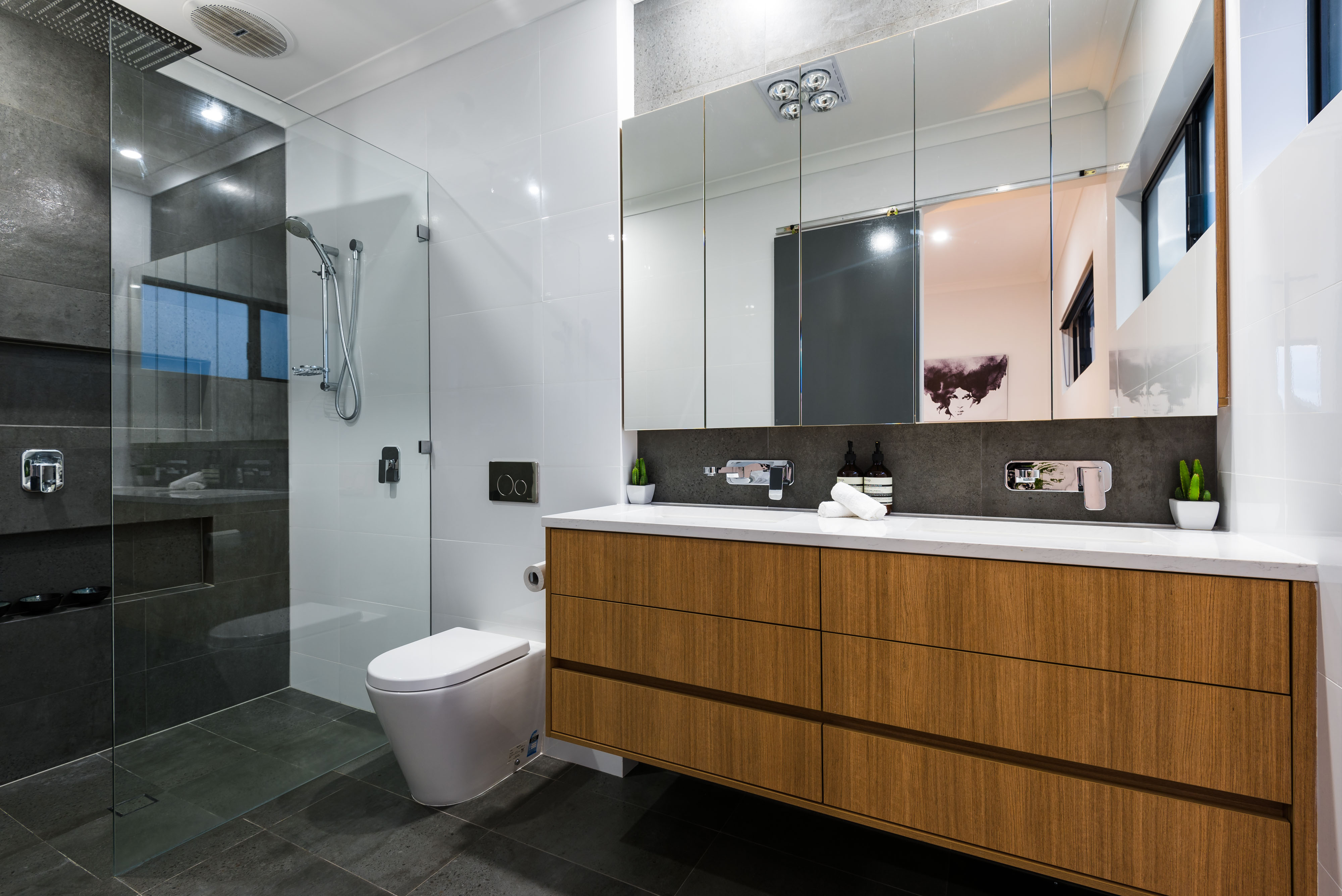 picture of a bathroom with transparent shower screens and mirrors